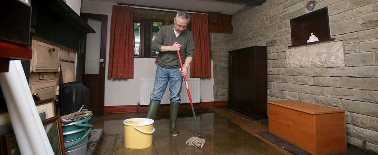 a man forlornly mops a flooded room