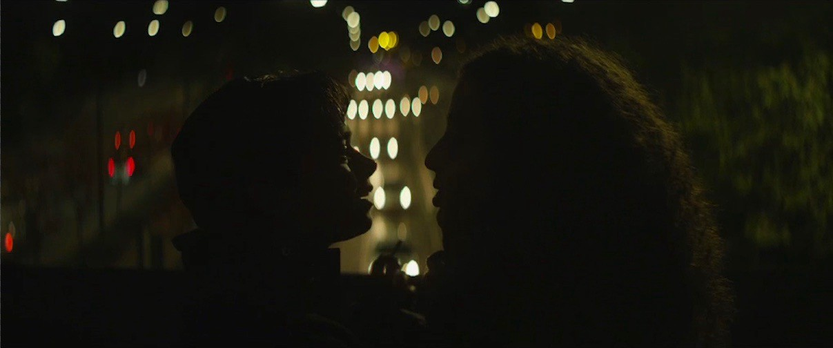 two young people facing each other in silouette at night, street lights can be seen behing them