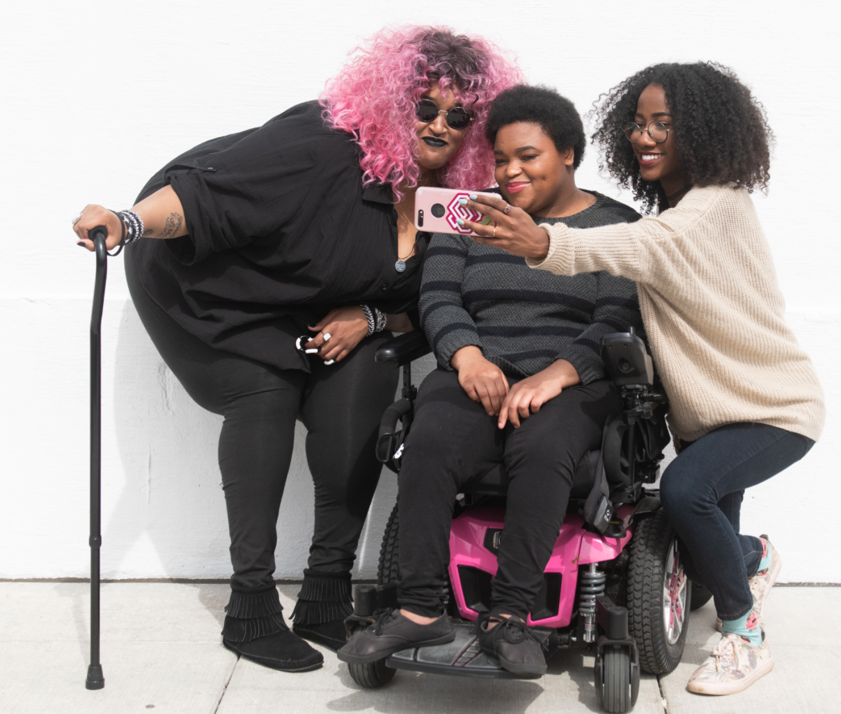 3 women leaning in together for a selfie. 1 holding a cane, 1 seated on a power wheelchair, and 1 woman hold a phone.