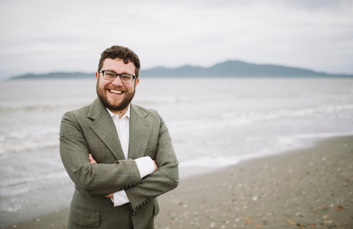 Asher, in a smart jacket suit smiling to camera, standing on the beach with Kāpiti island behind.