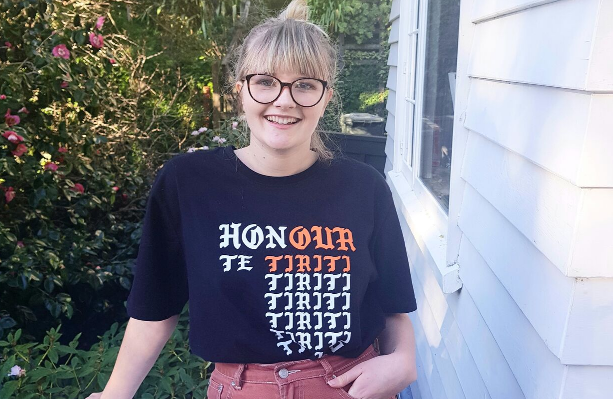 Victoria is standing outside a house, garden behind her looking at camera. Her tshirt says 'Honour Te Tiriti'.