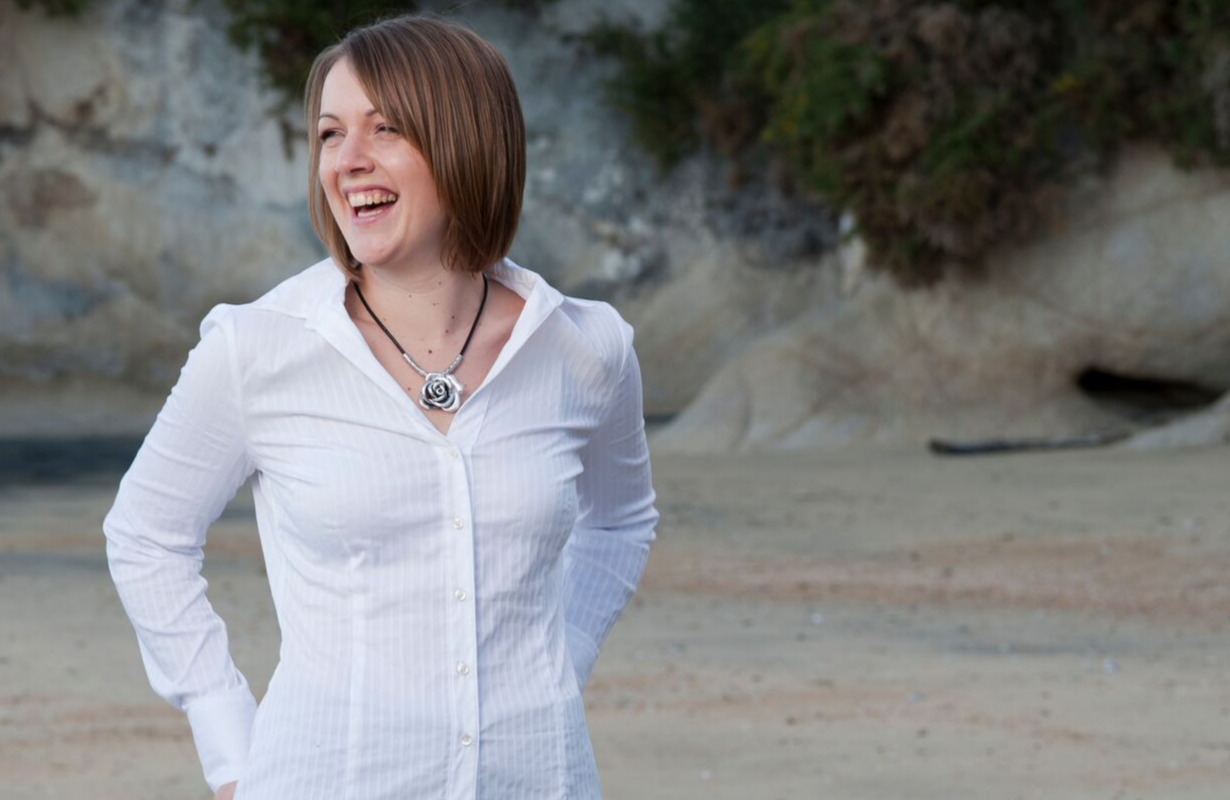 Julie laughing, looking off camera, at a beach with rocky background