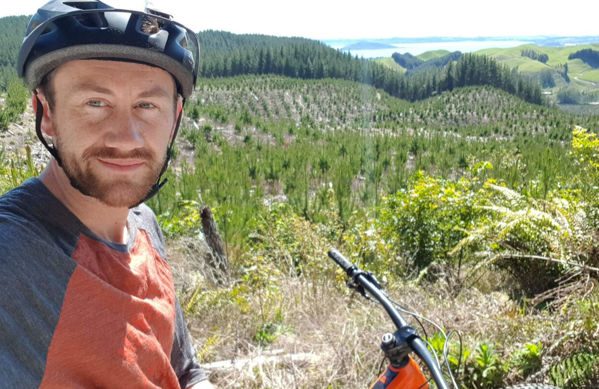 Ryan on a mountain bike with bike helmet on head, in from of countryside setting of green planted pine trees and a lake