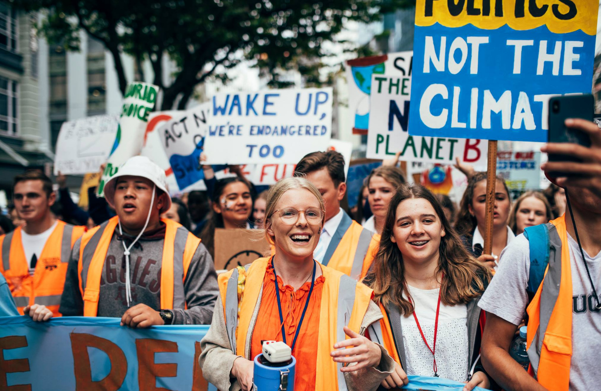 Sophie at the front of a climate strike march with lots of people in orange vests, holding a megaphone