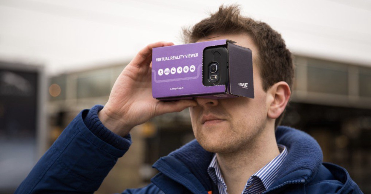 man holding cardboard Augmented Reality googles over eyes