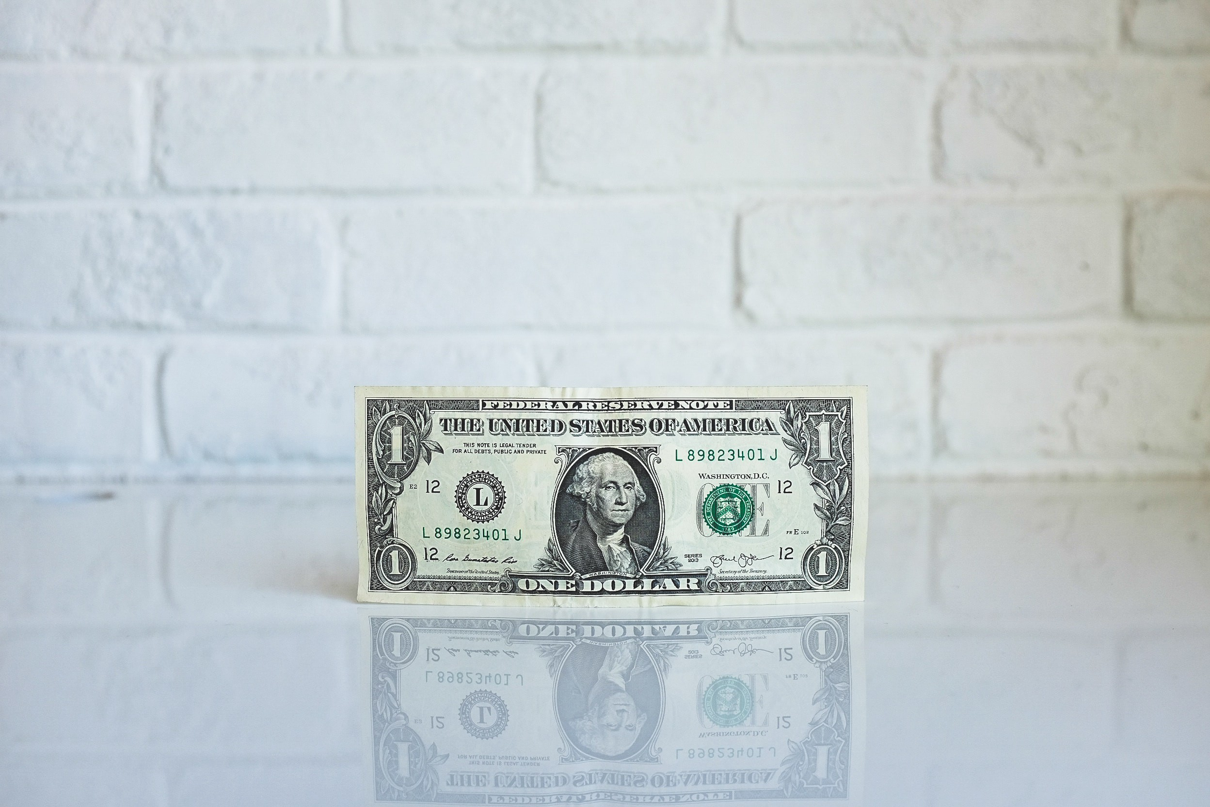 One dollar note reflecting on a shiny wall depicting ROI