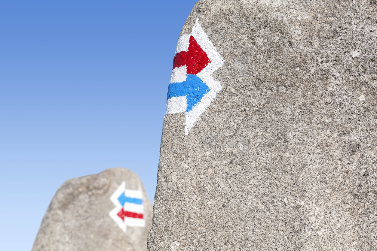 Image of trail signs painted on rock, choice or dilemma concept