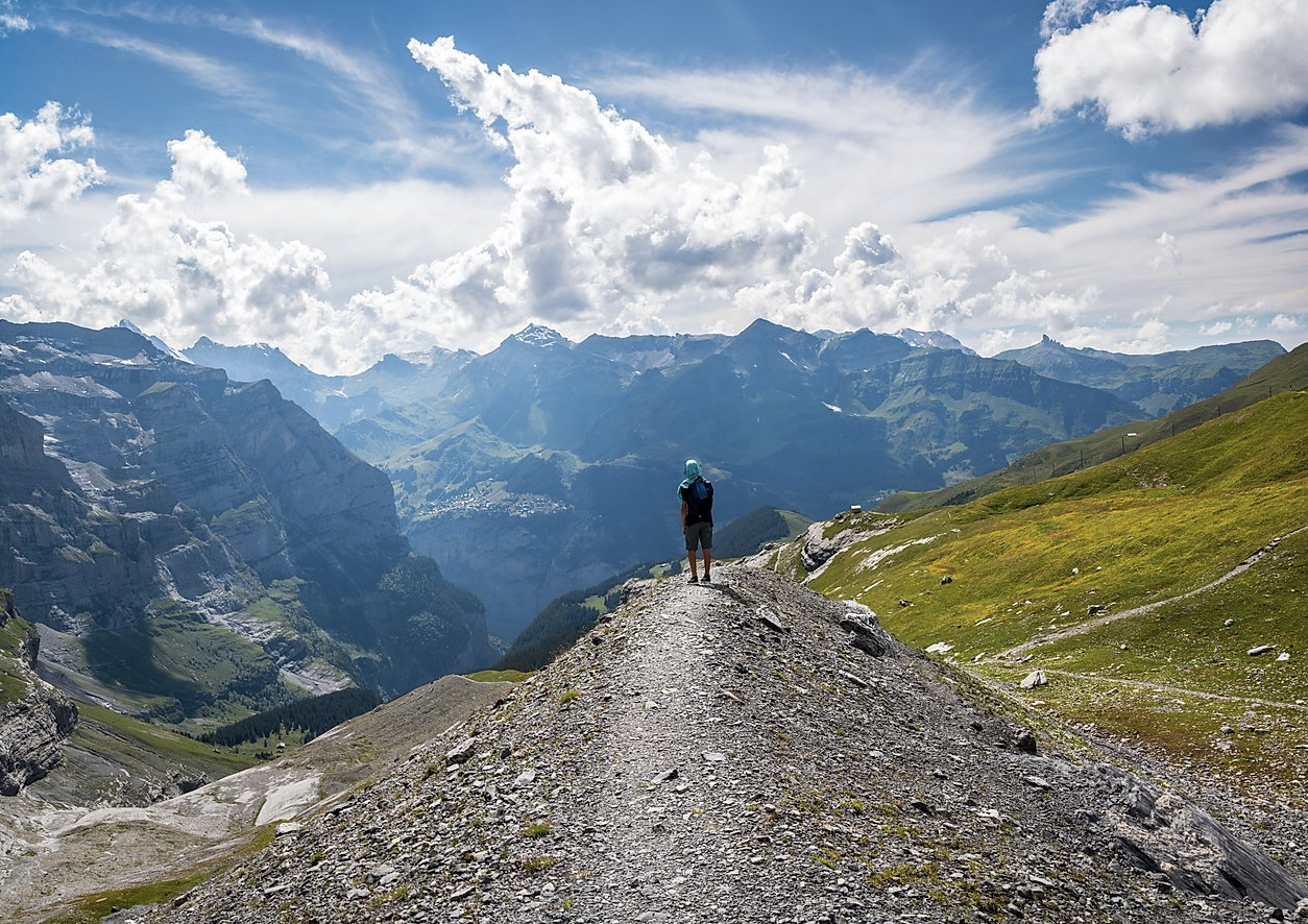 Photo of young man at the end of a trail, looking out into the distance of sky and mountains on a clear day.