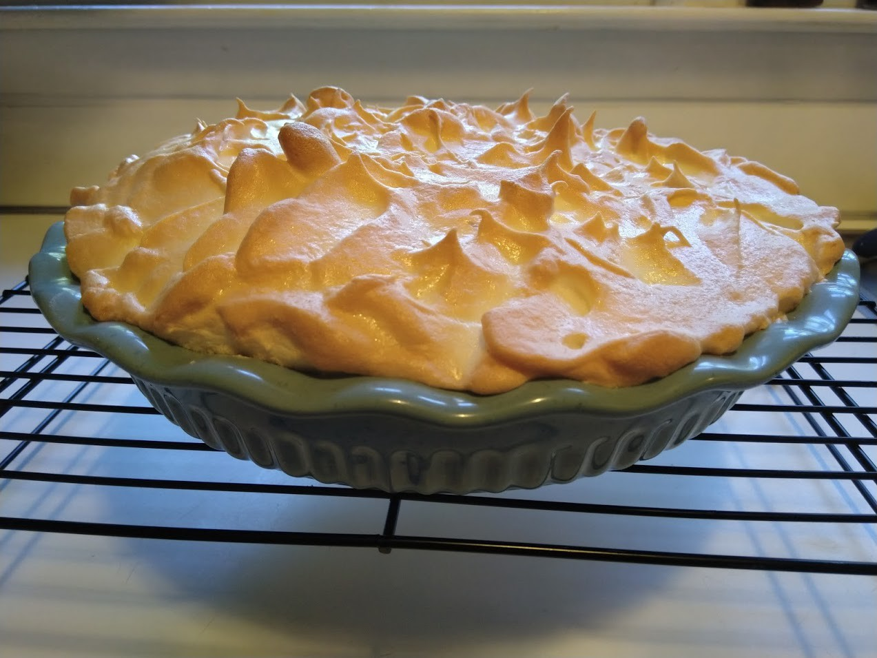 A golden brown merangue pie in a teal ceramic pie dish, cooling on a rack