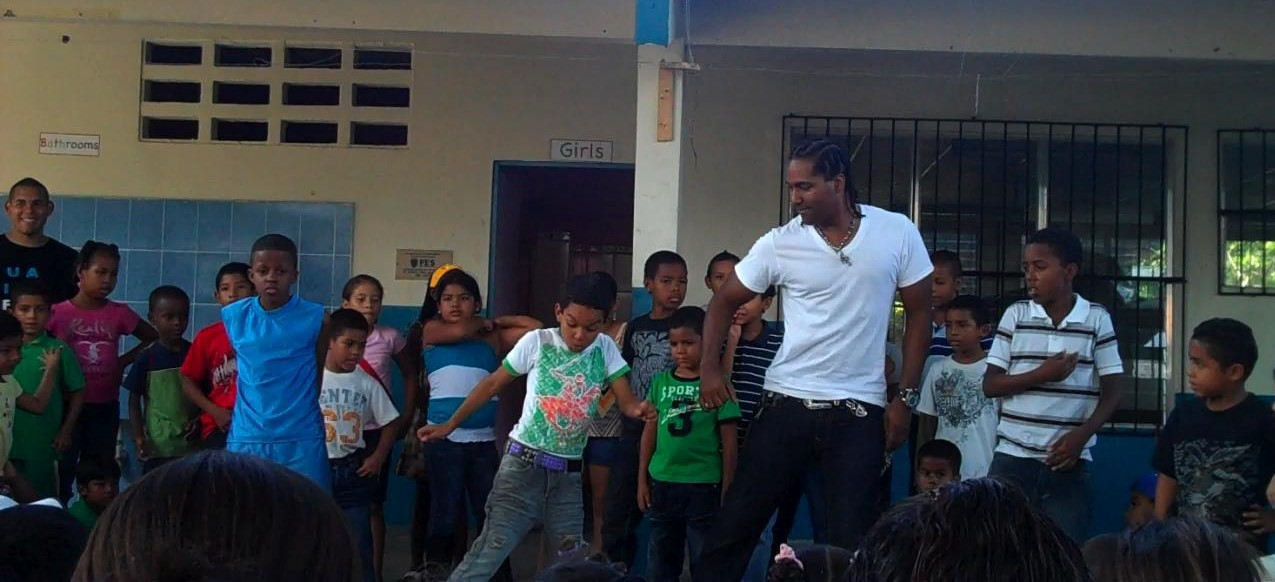 Man wearing a white t-shirt dances with a group of children in a courtyard