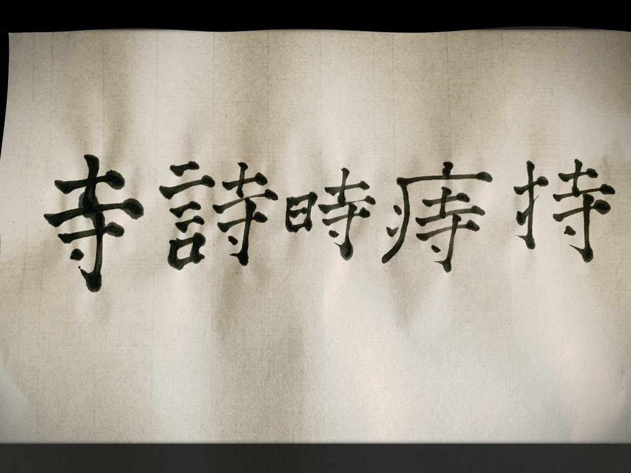 Five Chinese characters written out by the author using a traditional Chinese brush on rice paper.