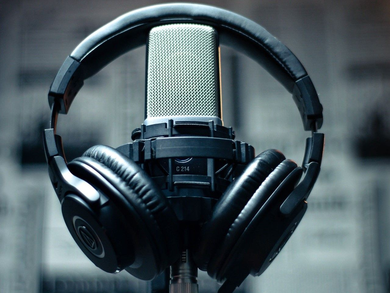 A photograph of headphones hung over a professional looking microphone, like you might expect for a recording studio or podcast