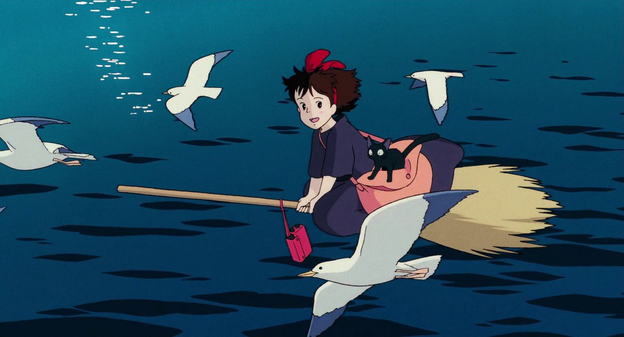 Kiki, from Kiki's Delivery Service, is flying over the water on her broom, orbited by seagulls.