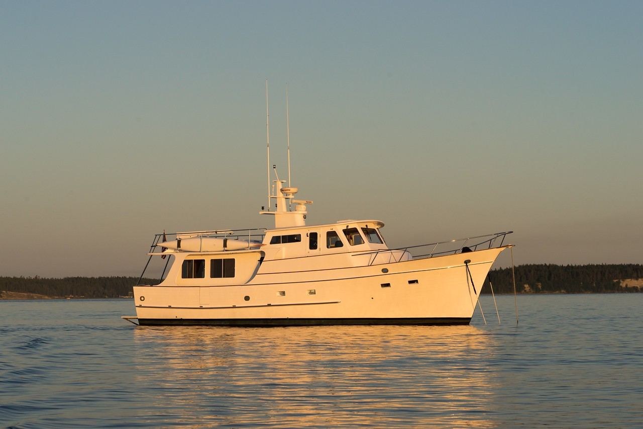 A large white ocean-going motor cruiser — a Grand Banks Alaskan 49 —rests at anchor in a golden sunset.