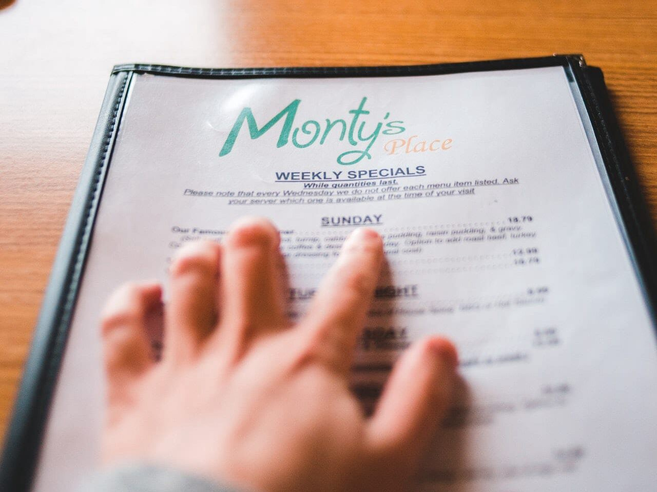 a hand scrolling across items on disposable menus