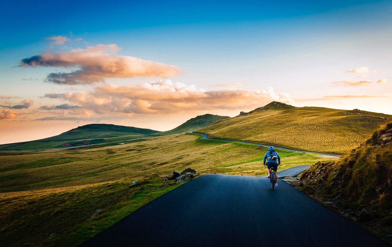 Man on a mountain road cycling towards the rising sun.