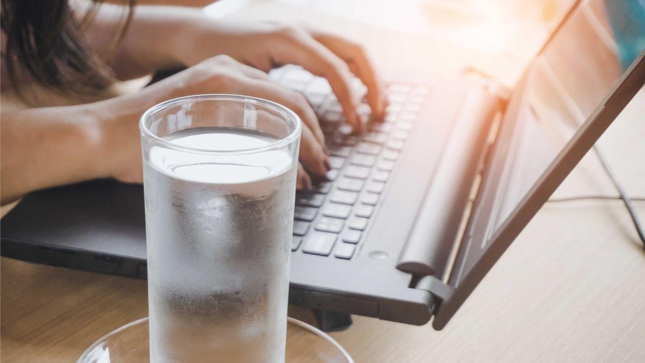 Frosty glass of water next to a person working on laptop