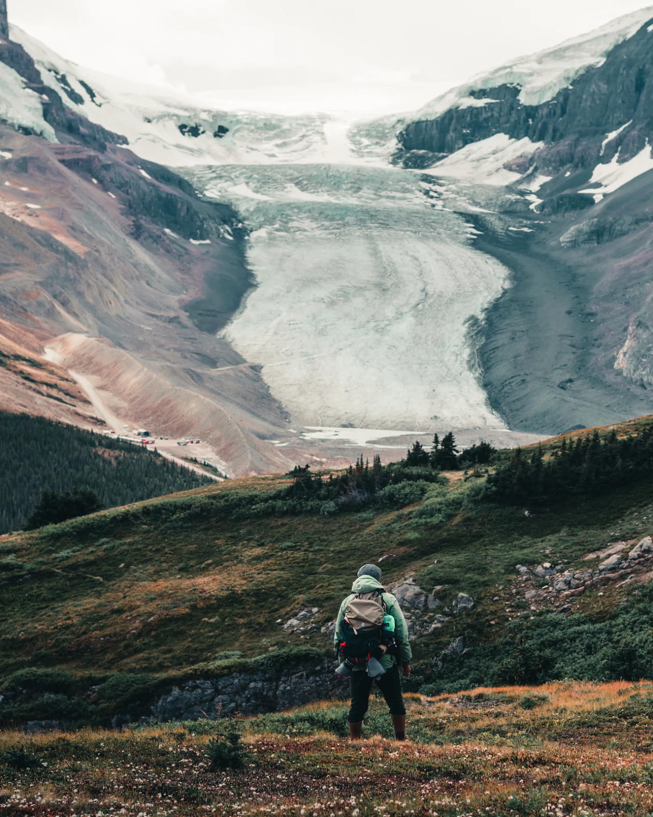 Someone looking up at a glacier.