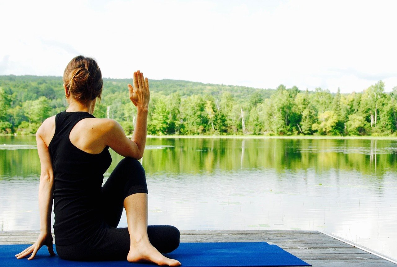 Woman doing yoga on a mat by a lake.