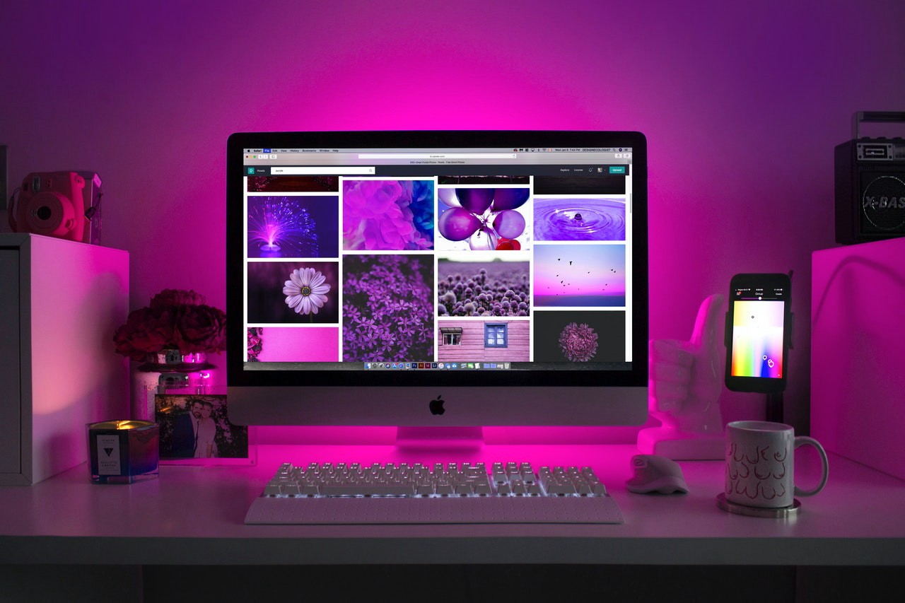 Imac on a white desk with pink accent colours all around