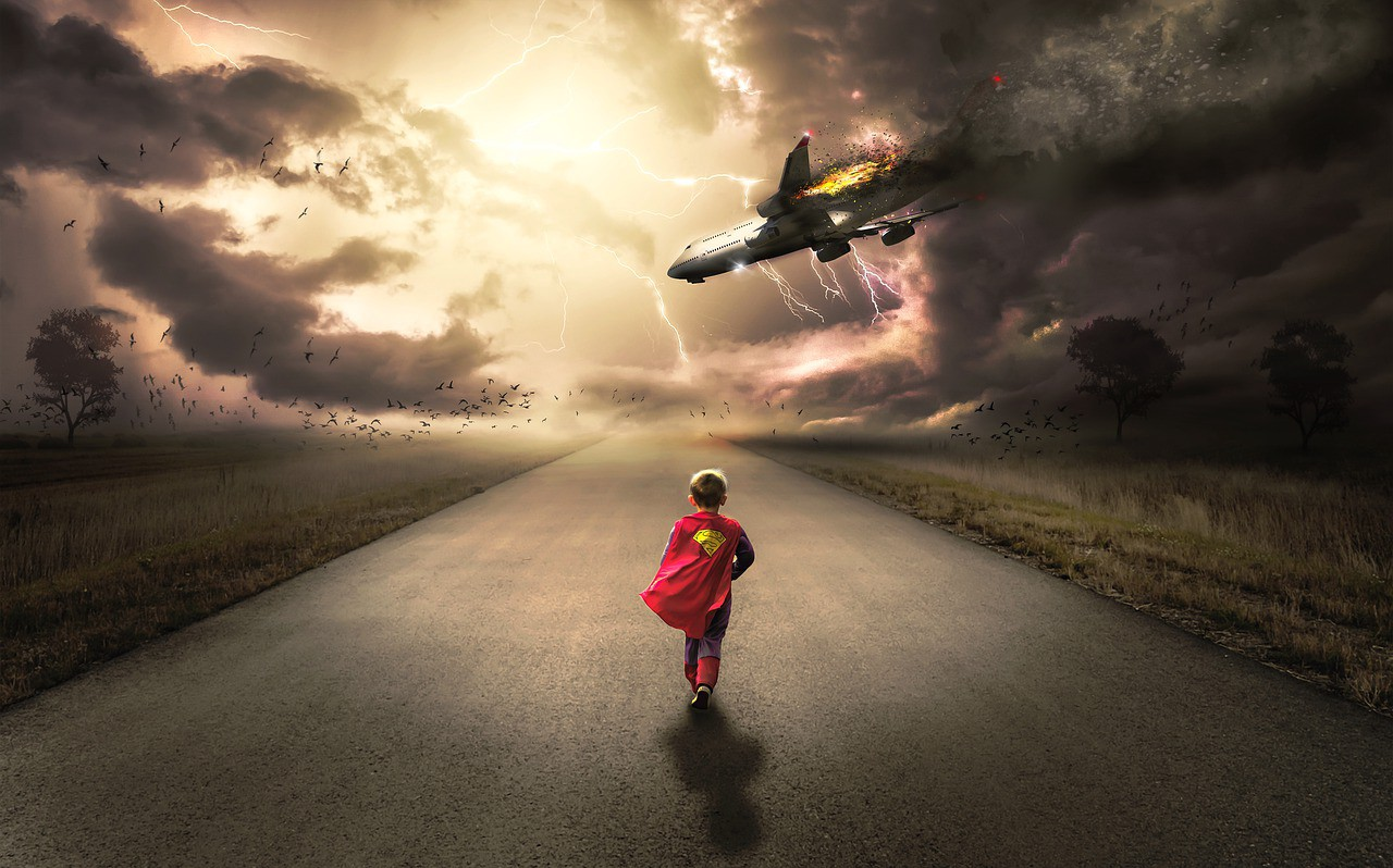 Boy dressed like superman running down an empty road toward a plane crash (plane being struck by lightning).