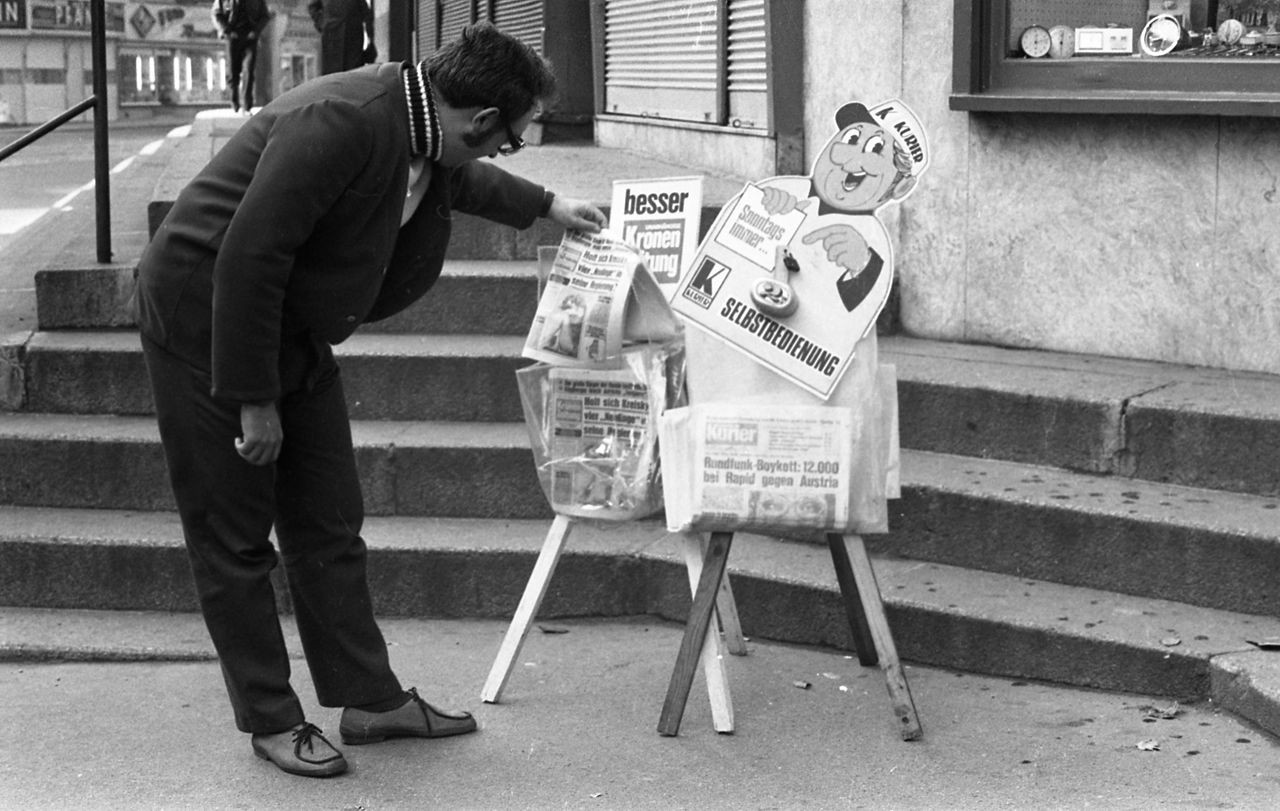 A black and white photo of a man looking at newspapers on a street corner in Vienna, Austria.