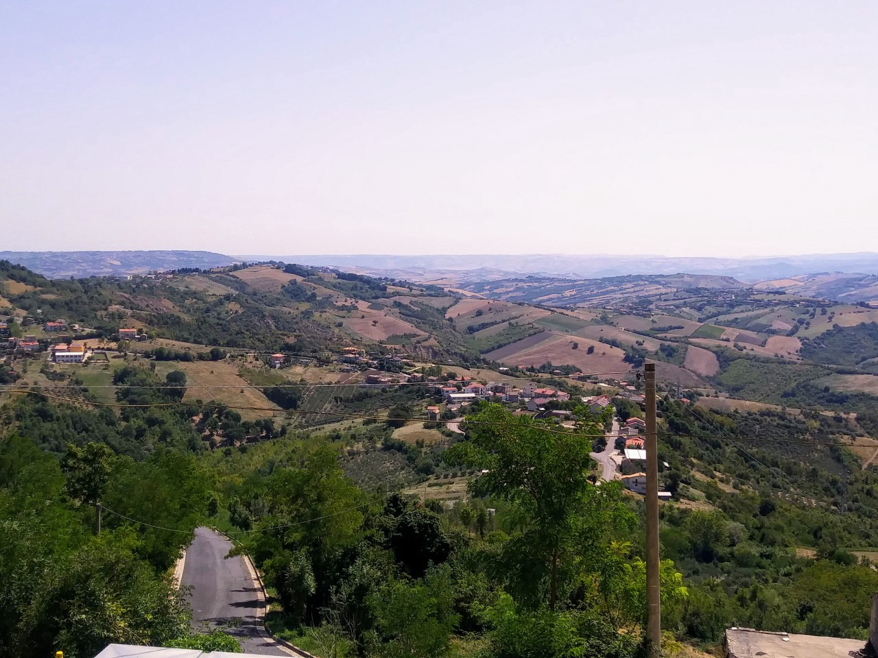 A panorama of Guardiagrele in Abruzzo, Italy shows green rolling hills and mountains.