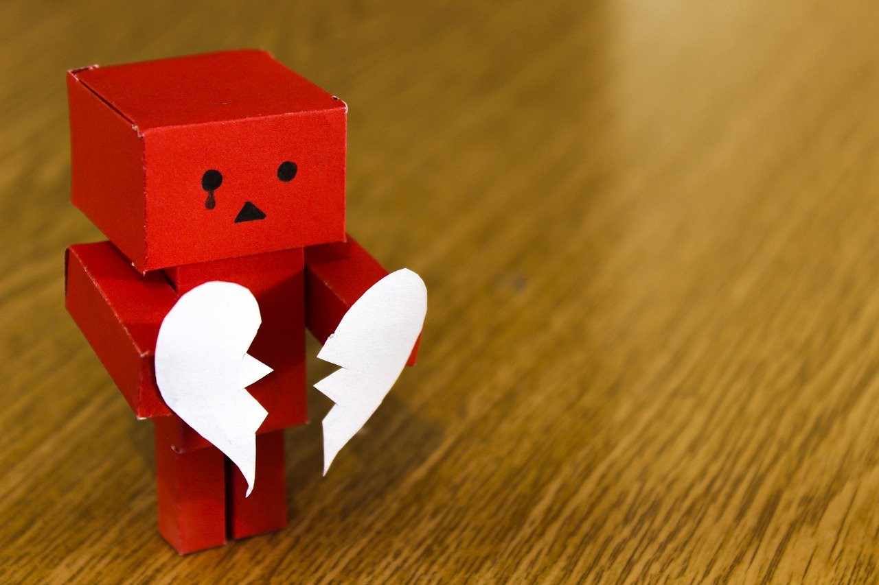 A red figure holding two halves of a broken heart Picture by Pexels via Pixabay