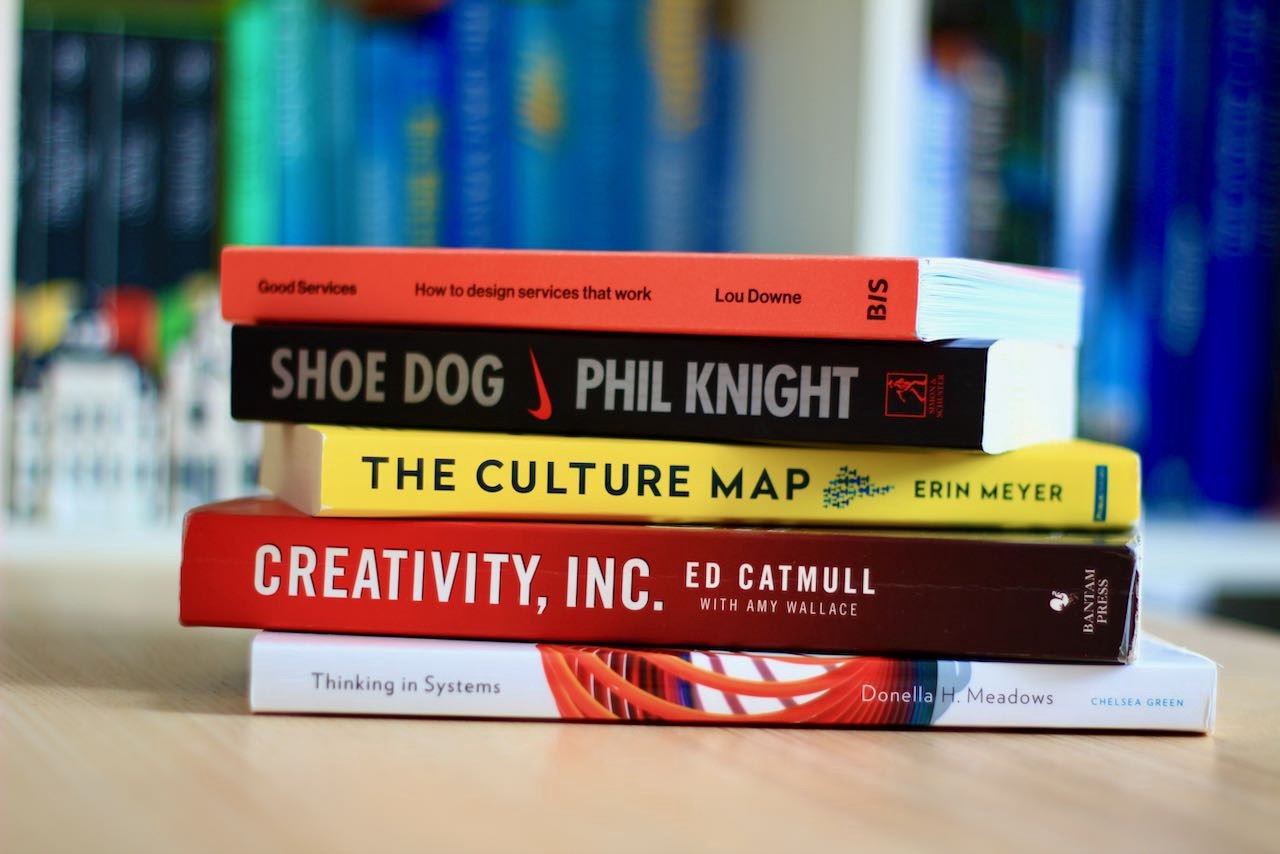 Stack of 5 recommended design books: Thinking in Systems, Creativity Inc, The Culture Map, Shoe Dog and Good Services