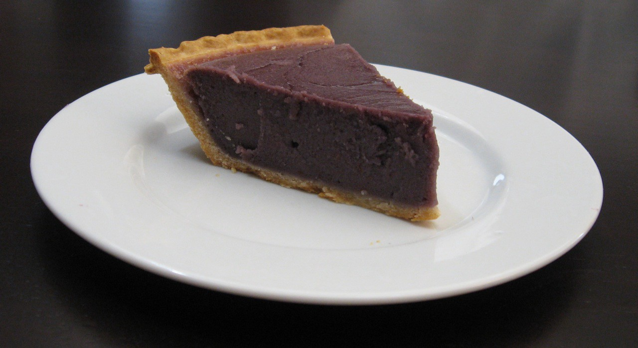 A close up of a slice of purple sweet potato pie on a white china plate.