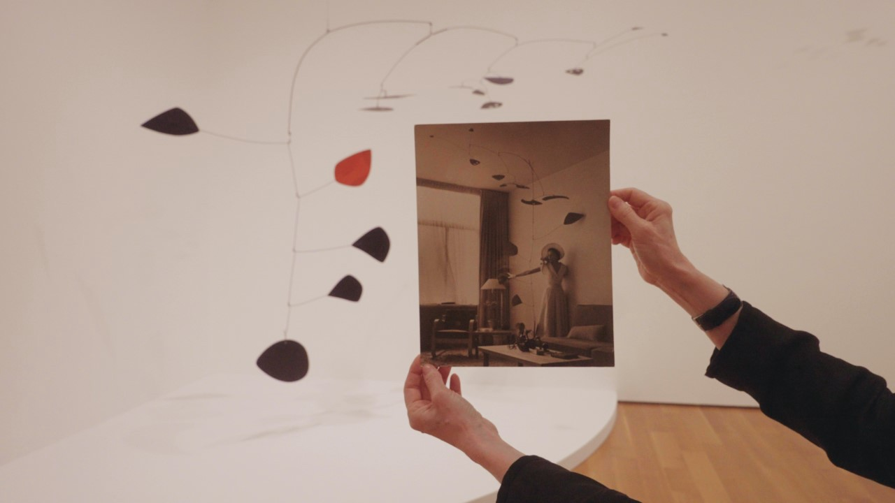 In front of a Calder mobile installed in a white-walled gallery, a woman's hands hold out a sepia-toned photograph of the same mobile installed in an apartment in the past.