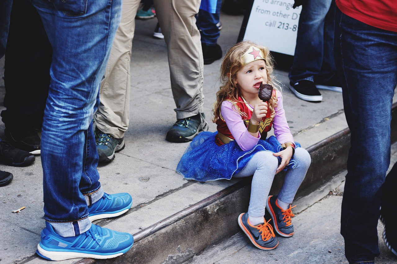A small girl dressed as Wonder Woman, sitting on a curb, surrounded by adults (legs only), and eating ice cream.