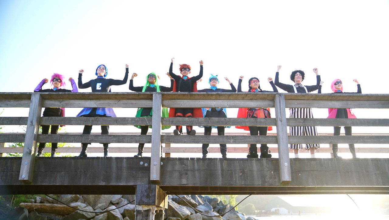 Six kids and two adults, dressed in colourful superhero costumes, are posing like heroes at the side of a wooden pier.
