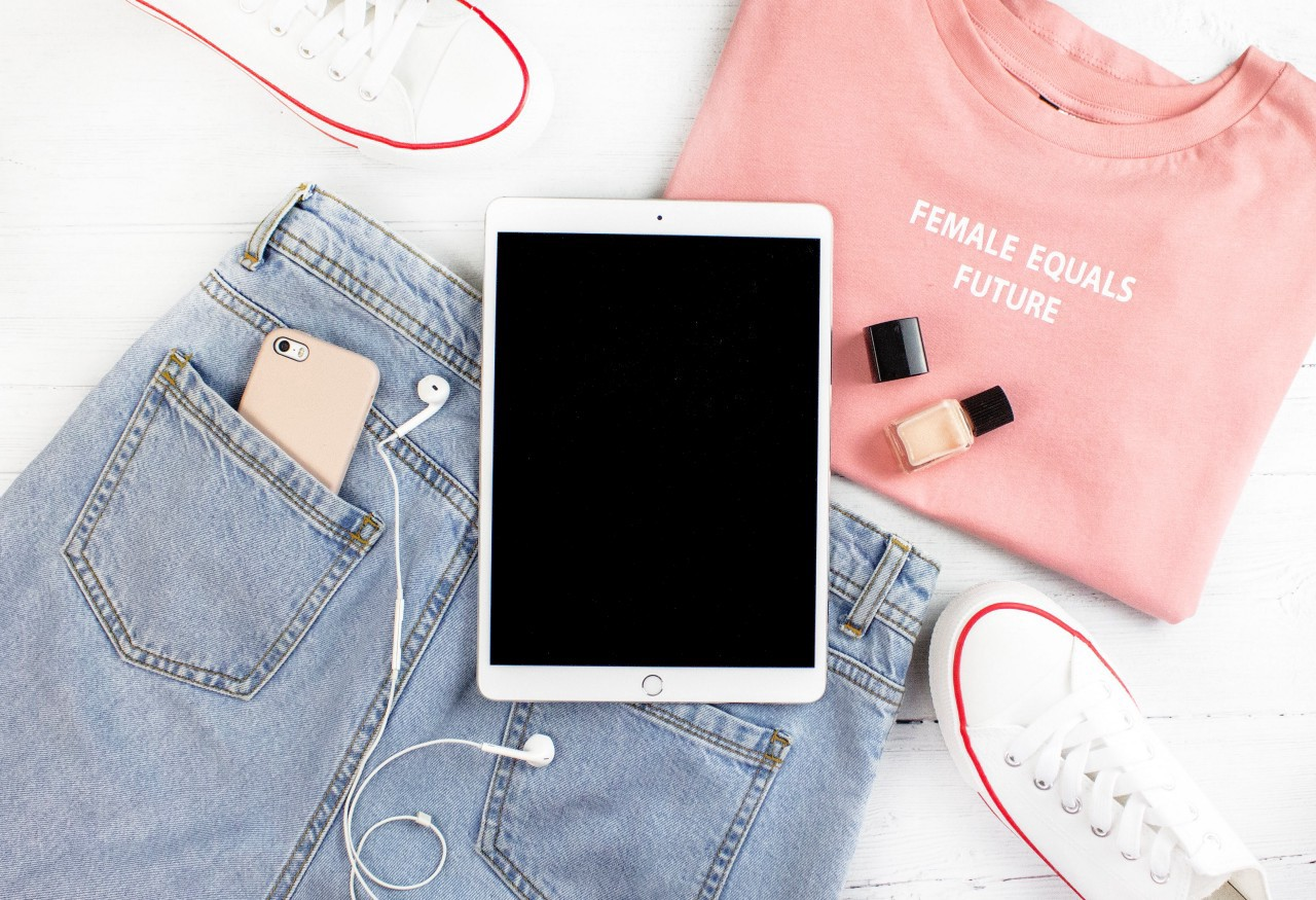 "A folded ""Female equals future"" shirt, jeans with a phone in the back pocket, white canvas shoes, nail polish, and an iPad."
