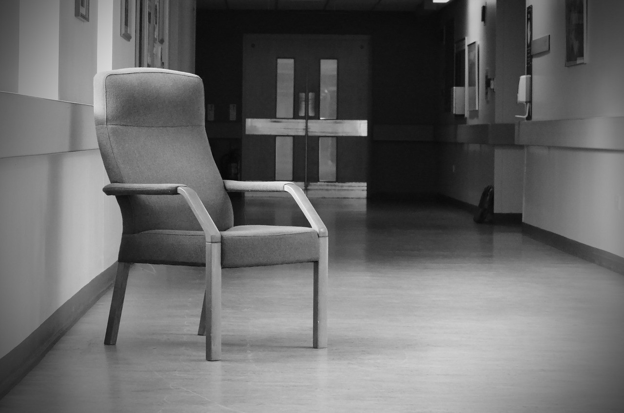 Black & White Picture of a Hospital corridor with a chair in the foreground