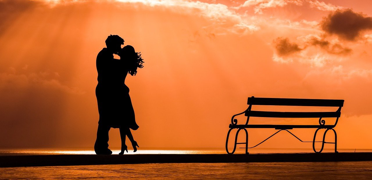 Image of the silhoutte of a couple kissing with the sunset as a background