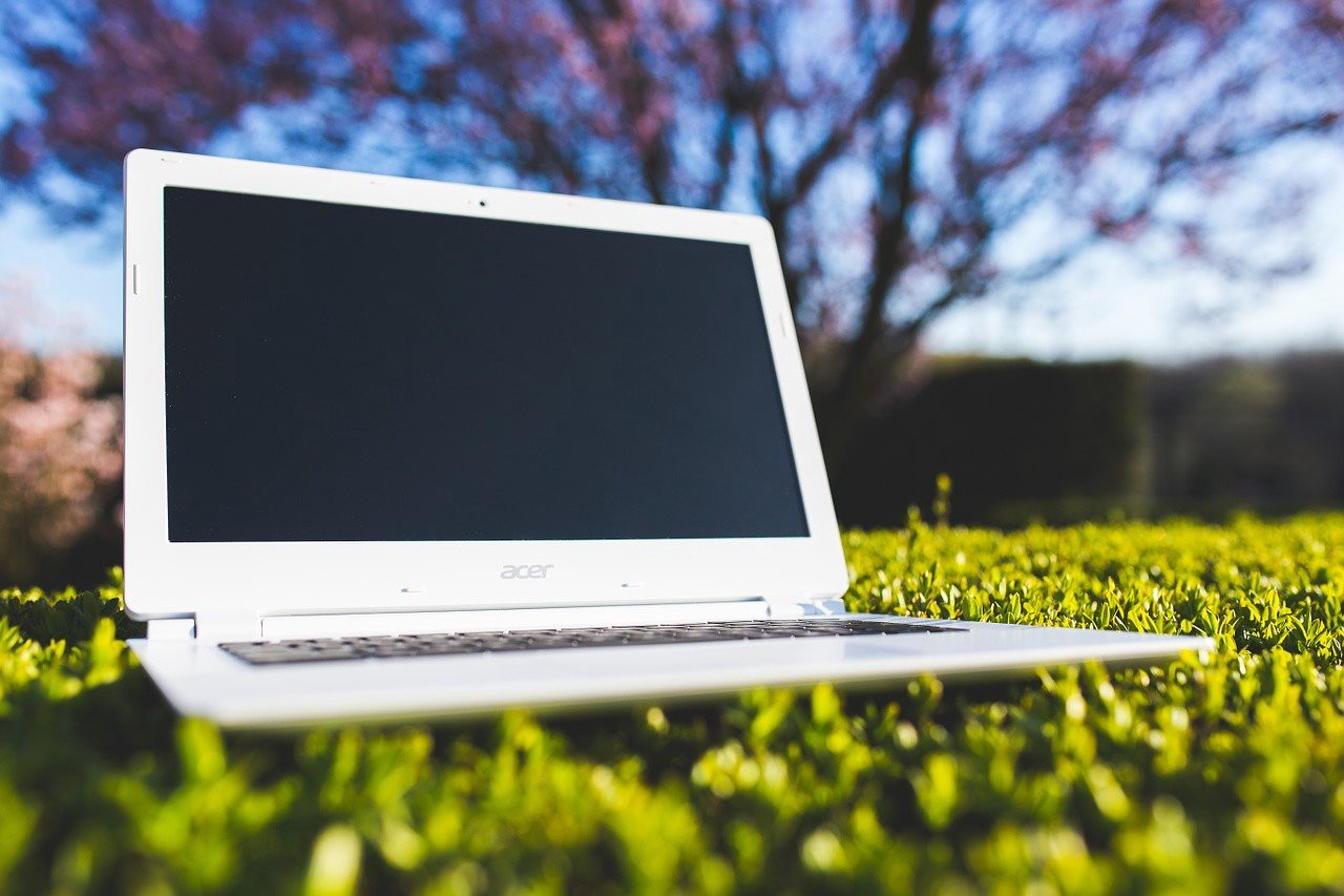 Acer laptop sitting on bright green grass outside.