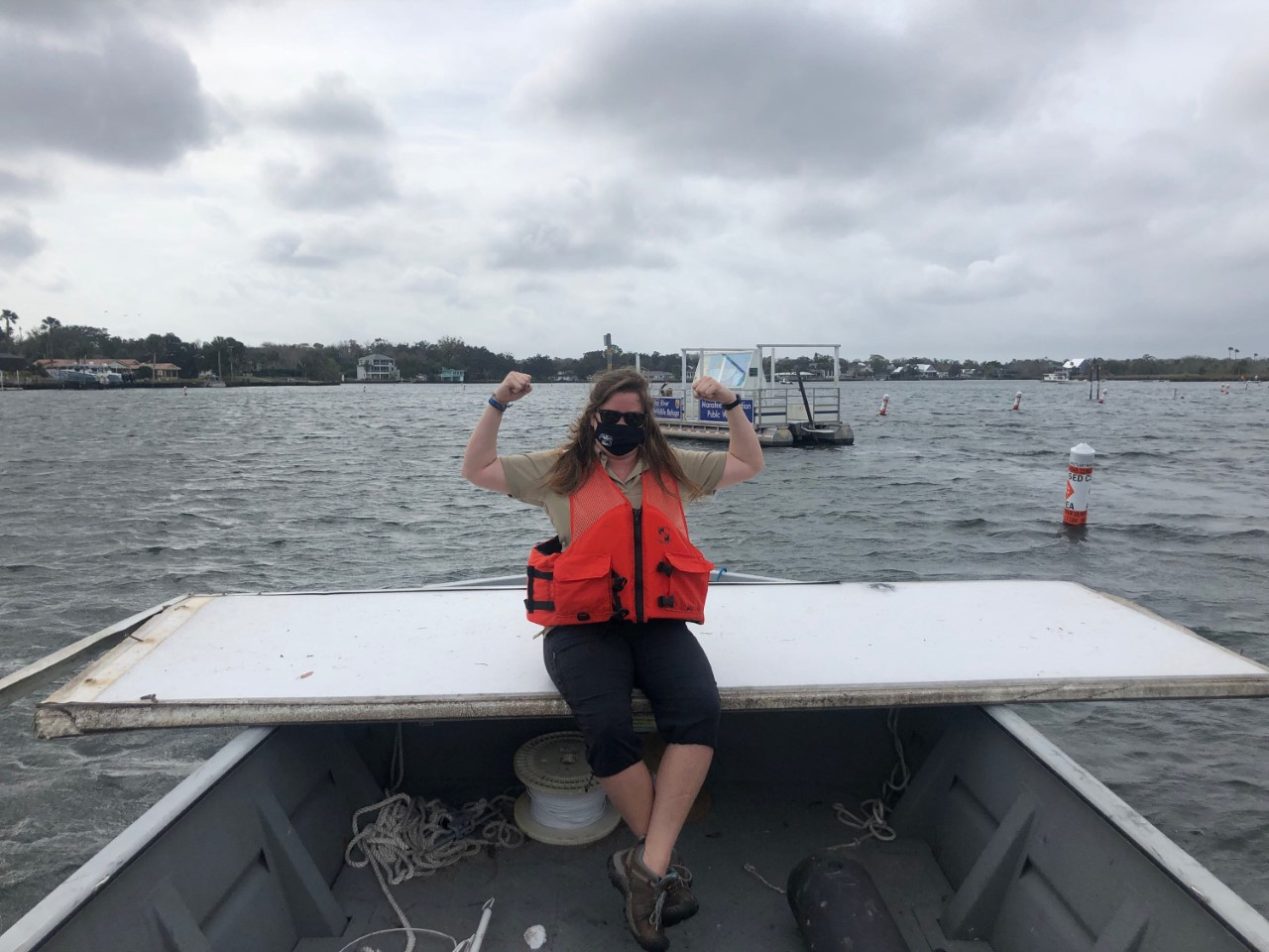 woman on boat in life vest and mask raises arms in triumph