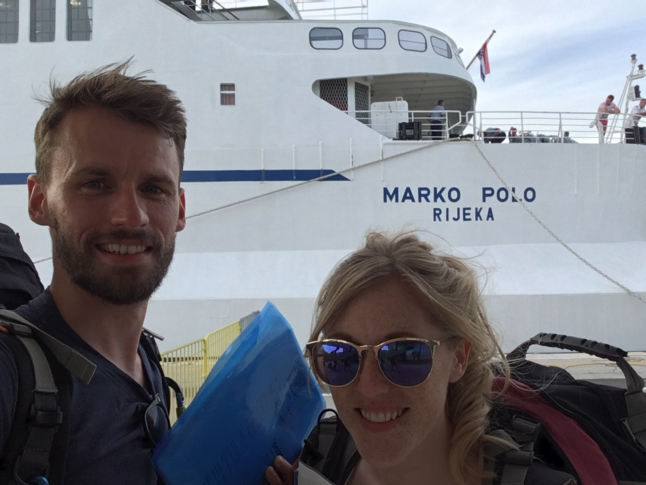 Two people with a ferry in the background