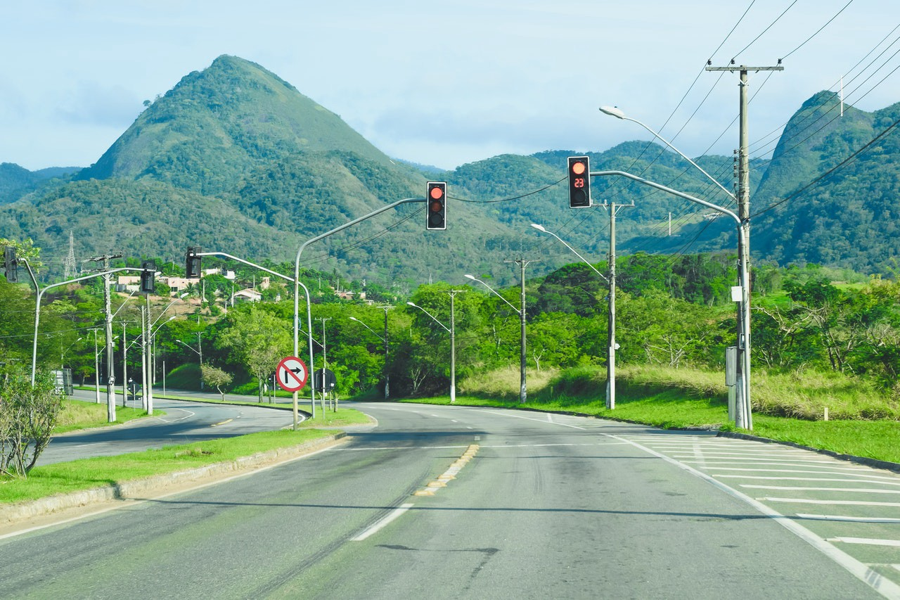 An empty road with traffic lights, trees and a mountain in the distance