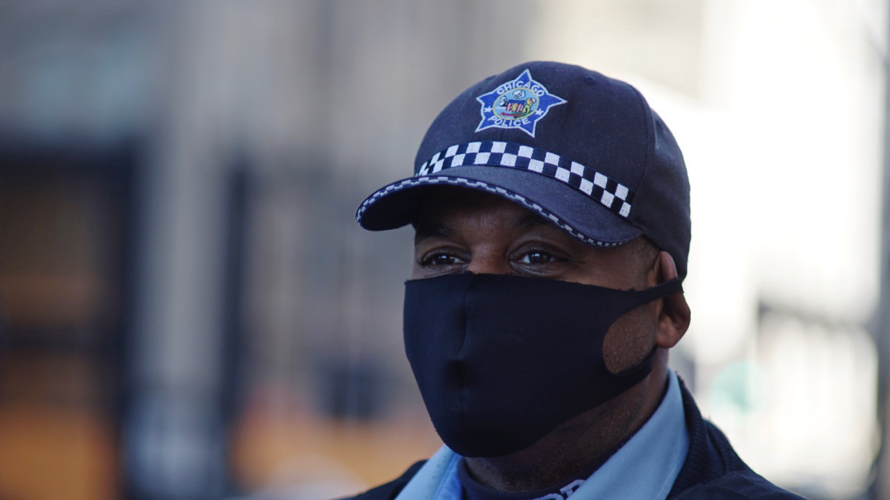 Chicago's finest stands with a black mask near Michigan Avenue, keeping watch over the city.