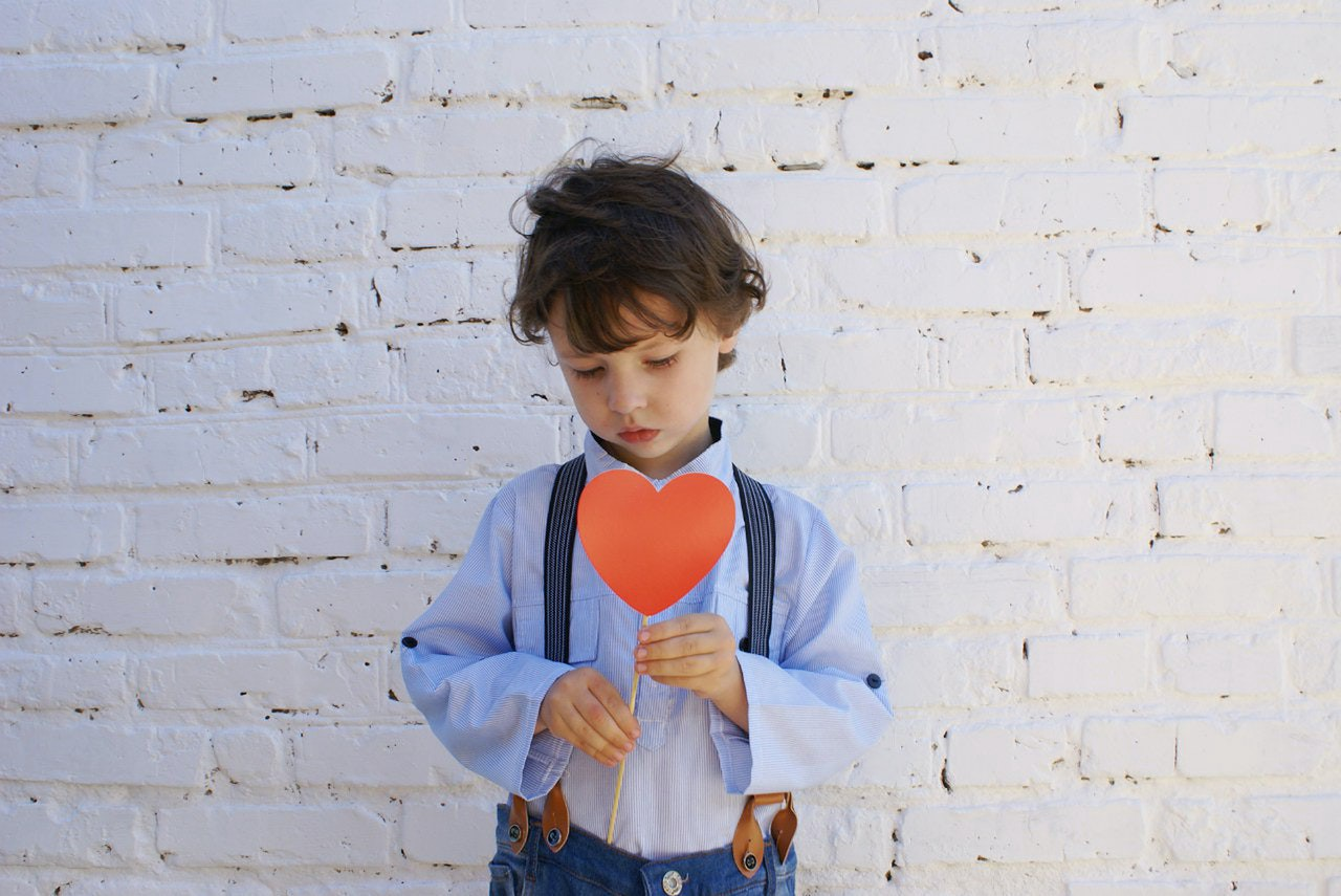 small boy holding a red, paper heart, standing in front of a white brick wall