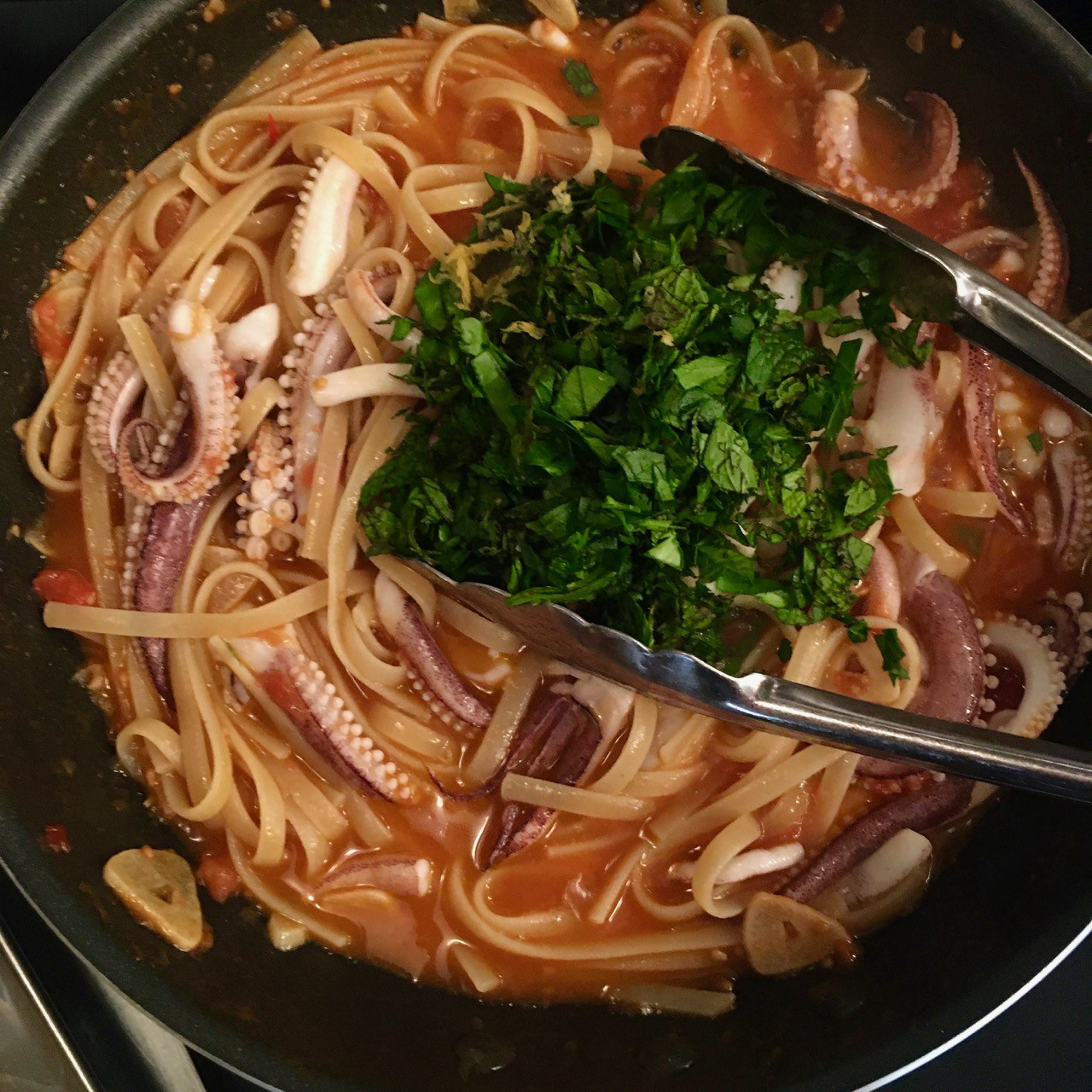Overhead shot of a pan of linguini in sauce with squid tentacles on top, being topped with chopped herbs.