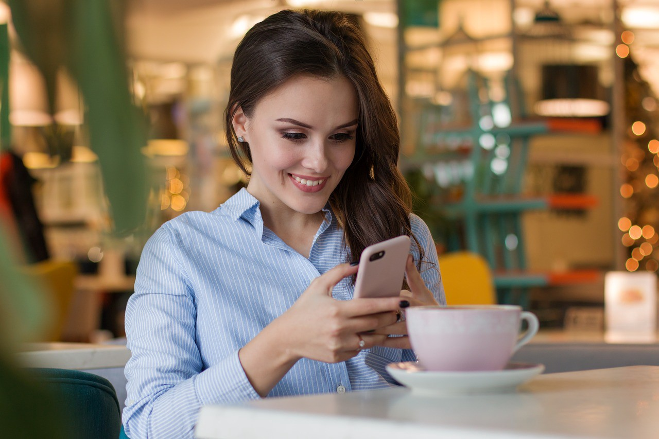 Smiling woman excitedly looking at phone in coffee shop.