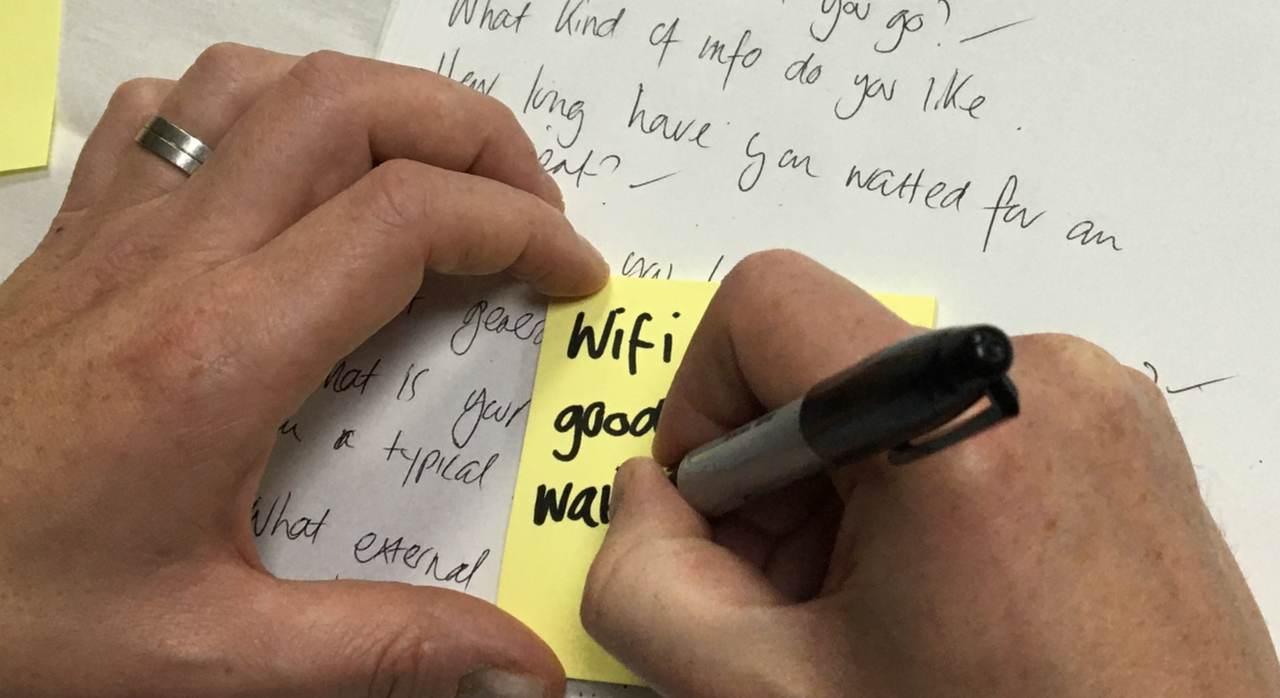 Participant writing user interview notes on a sticky note.