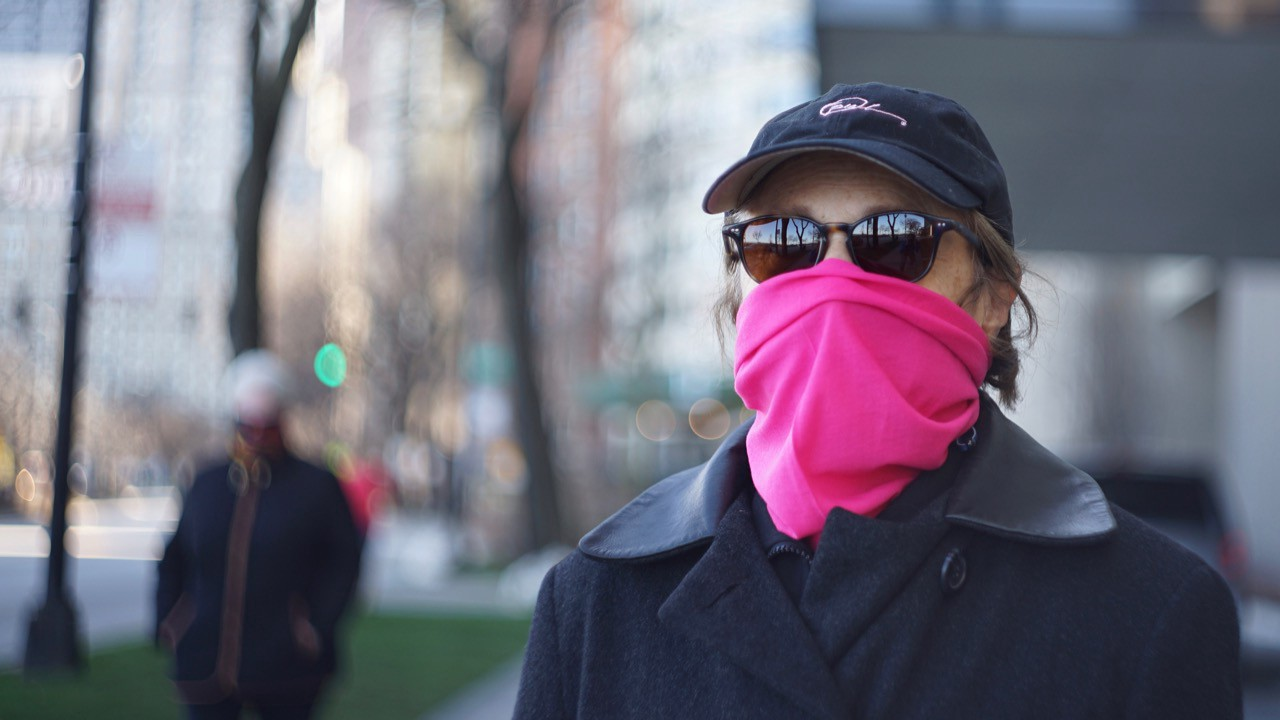 A woman wears a pink buff while out for a walk on a sunny, cool day.