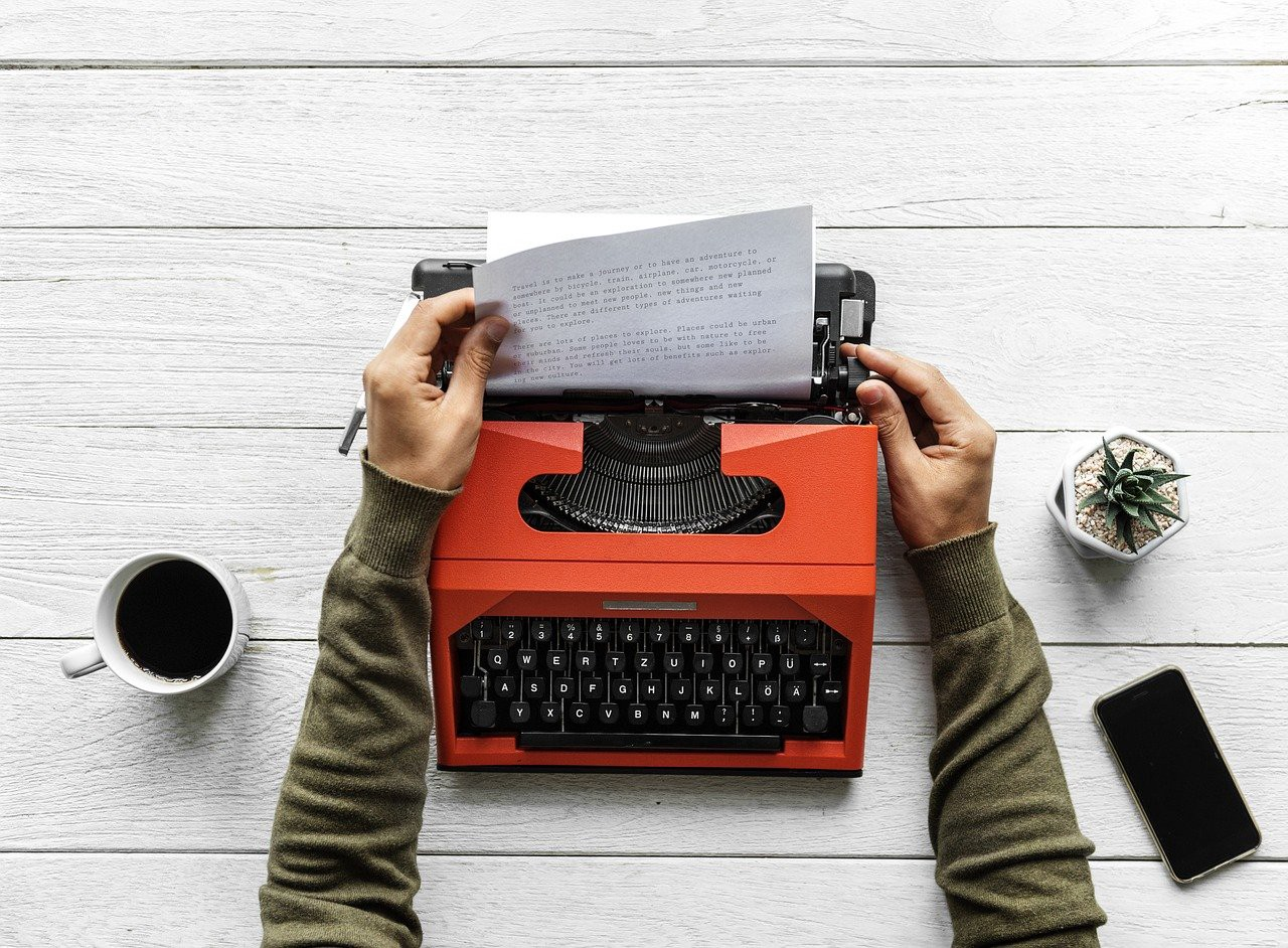 person's hands removing paper from an orange typewriter on a white surface with a cup on left, phone and plant on right