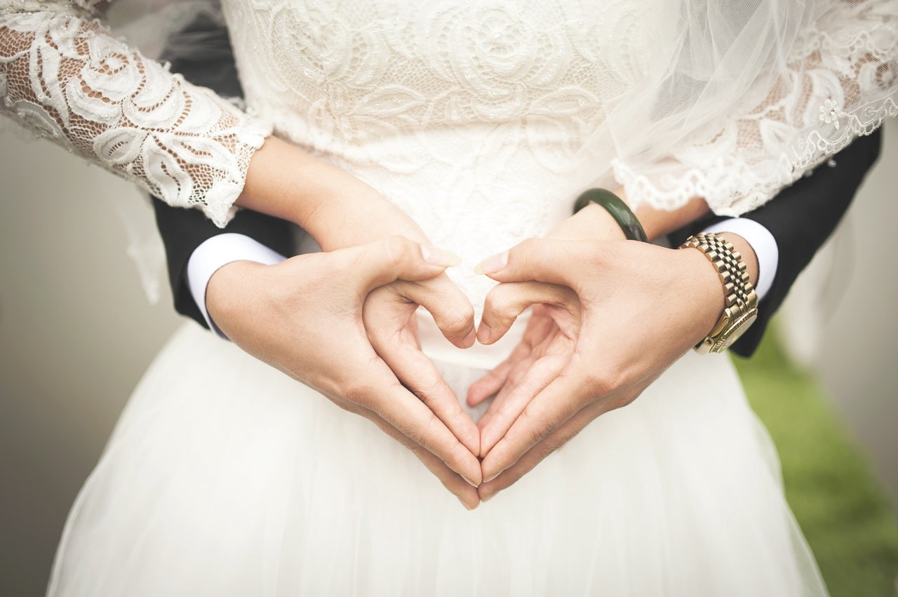 Close-up of bride and groom's hands which are forming the shape of a heart
