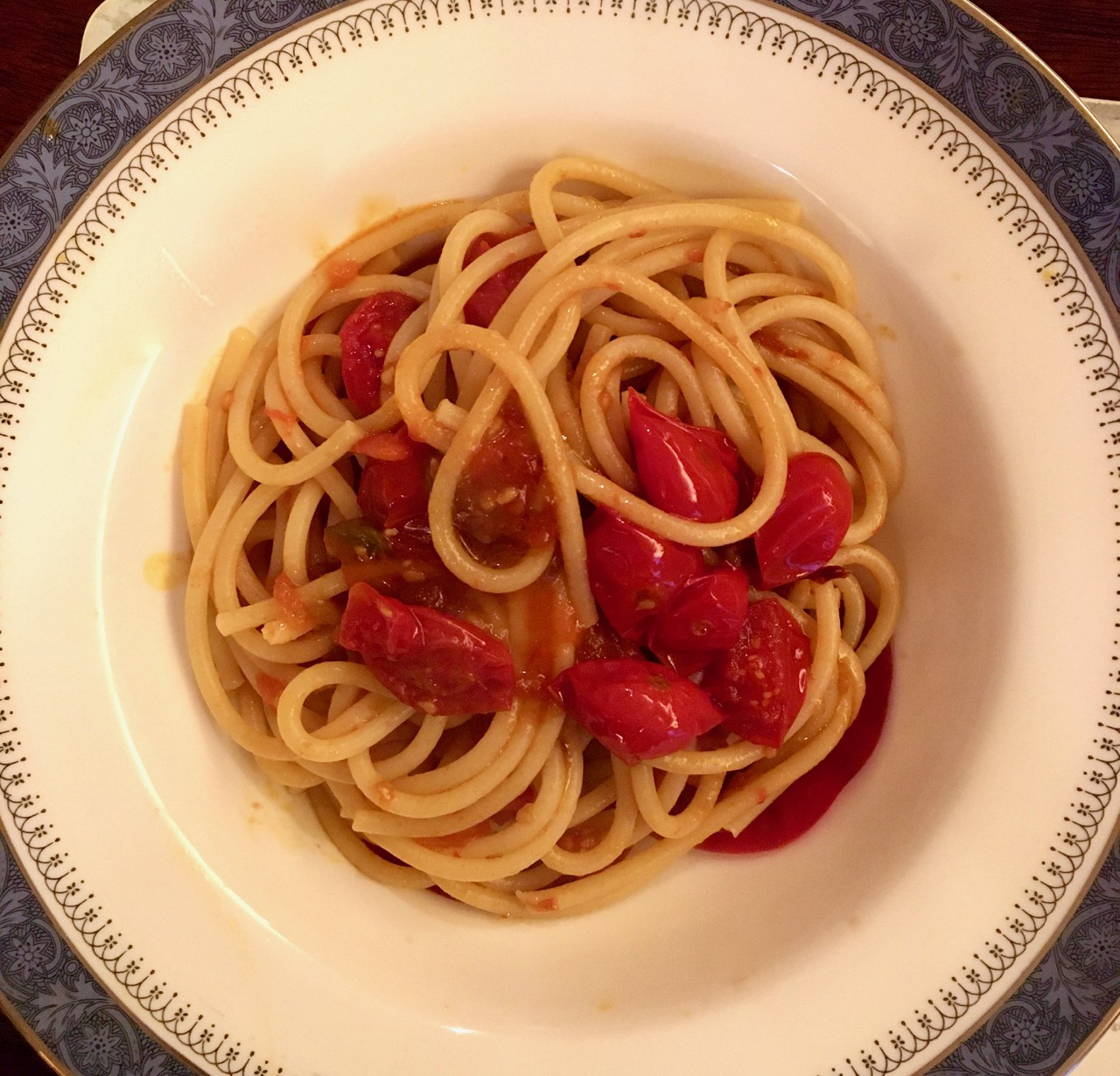 A bowl of pasta with fresh and cooked tomatoes.