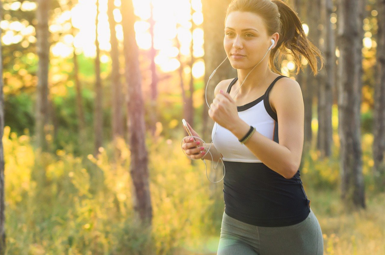 woman running through forest of trees at sunrise.